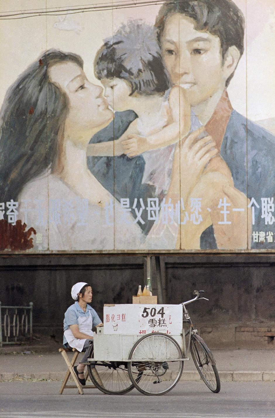 A street vendor awaits customers beneath a billboard exhorting people to adhere to China's one-child policy, in Lanzhou, China on August 4, 1988. China recently lifted the policy, allowing families to have a second child. Mark Avery/AP